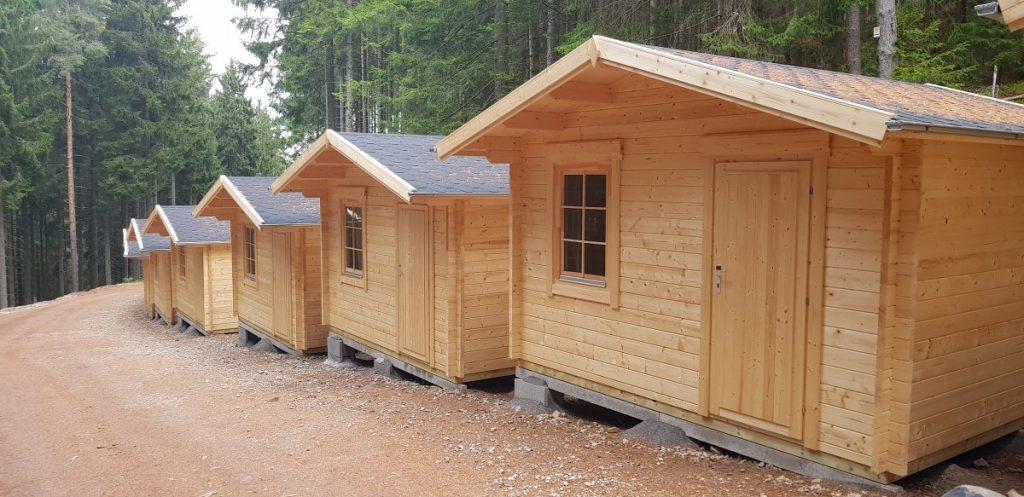 """Ob Sie nun bereits Eigentümer eines Campingplatzes sind und diesen mit neuen Angeboten wie z.B. einem Restaurant, einem Seminarraum oder zusätzlichen Übernachtungsmöglichkeiten erweitern wollen, erst in der Planung eines neues Campingplatzes sind oder aber im eigenen Garten einfach ein Gästehaus mit ein oder zwei Zimmern errichten wollen, das Sie dann vermieten (z.B. AirBnb), unsere mittelgroßen und großen Holzhäuser und Blockhütten mit einer Wandstärke von 58, 70 und 92 mm sind genau das Richtige für Sie! Verschiedene Modelle für unterschiedliche Zwecke Um den unterschiedlichen Bedürfnissen unser Kunden gerecht zu werden, bieten wir eine große Auswahl an Holzhäusern und Blockhäusern in verschieden Größen und zu verschiedenen Preisen an. Falls Sie einer Familie mit ein oder zwei Kindern eine Übernachtungsmöglichkeit anbieten wollen, bieten sich unsere Modelle im Studio-Stil """"Malaga I"""" und """"Malaga II"""" mit einem separaten Raum für die Installation einer Dusche und Toilette an. Auch das kompakte Ein-Schlafzimmer-Modell """"Hansa Holiday Camping"""" mit einer 3x3 m großen Veranda wird bei Ihren Kunden gefallen finden. Diese Modelle erhalten Sie für 7000 bis 8000 Euro, und unser Montage-Team kann sie für ca. 2000 Euro aufbauen. Jedes dieser Modelle bietet ca. 20 Quadratmeter Wohnfläche. Mehr Raum bieten die Modelle """"Holiday H"""" und """"Holiday J"""" mit jeweils 40 Quadratmetern. Sie verfügen über einen großen Wohn- und Kochbereich, einen Duschraum sowie ein großzügiges, 3x4 m großes Schlafzimmer. Das Modell """"Ireland"""" bietet 43 Quadratmeter Wohn- und Essfläche mit einem Duschraum und zwei Schlafzimmern. Für diese Modelle müssen Sie mit 12.000 bis 13.000 Euro rechnen. Unser Montageteam baut diese Modelle innerhalb von drei Tagen für ca. 3000 Euro auf. Unsere ganz großen Modelle verfügen über eine Fläche von 50 bis 100 Quadratmetern und kosten zwischen 15.000 und 20.000 Euro. Es handelt sich um geräumige Ferienhütten mit zwei bis drei Schlafzimmern, die einen angenehmen Aufenthalt für s"""
